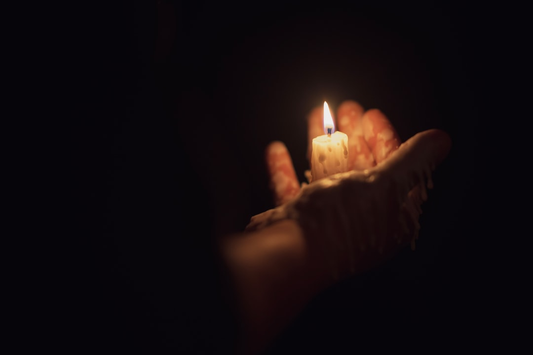 A hand holding a lit candle in a dark room